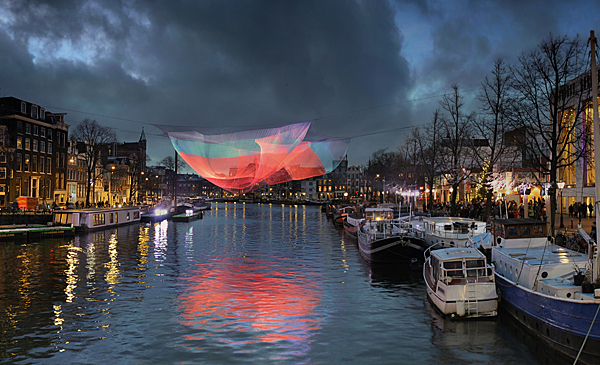 "Janet Echelman ""1.26"" 2012-2013, 230? x 63? x 30?, installation view over the Amstel River during the Amsterdam Light Festival, Spectra® high-tenacity polyester fiber and lighting, machine knotting. CREDITS: Client: City of Phoenix Office of Arts and Culture. Studio Echelman Team: Philip Speranza (Design Support), Melanie Rose Peterson (Conceptual Design/Development), Rachel Kaede Newsam (Design Support). Fabrication & Project Engineering: CAID Industries (Tuscon, AZ). Net Engineering: Buro Happold (New York). Aeronautical Engineering: Peter Heppel Associates (Paris). Consultant: Esperanza Architecture (New York). Steel Structure Engineering: M3 Engineering (Tuscon, AZ). Lighting: Vox Arts (Baltimore, MD). Structural Erection: Nexus Steel. Sculptural Foundations: Foresite Design (Berkley, MI). Photo: Ben Visbeek."