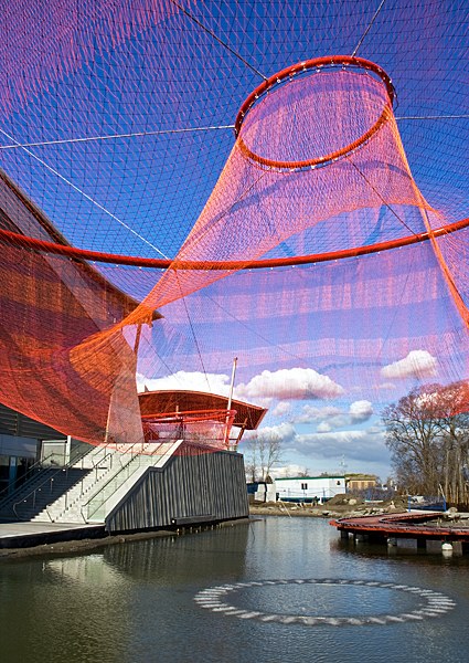 "Janet Echelman ""Water Sky Garden"" 2009, total garden area about 75,000 sq. ft., installation view outside the Richmond Olympic Oval in Vancouver, British Columbia, TENARA® Architectural fiber net forms hung from painted galvanized rings, cedar bridge, fountains, programmed lighting. CREDITS: Client: City of Richmond Public Art Program. Architect: Hotson Bakker Boniface Haden Architects + Urbansites (Vancouver, BC). Studio Echelman Team: Philip Speranza (Design Support), Melanie Rose Peterson (Design Support), Pachel Kaede Newsam (Design Support). Landscape Architect: Phillips Farevaag Smallenberg (Vancouver, BC). Net Engineering: Buro Happold (New York). Aeronautical Engineering: Peter Heppel Associates (Paris). Structural Engineer: Fast + Epp Structural Engineers (Vancouver, BC). Consultant: Speranza Architecture (New York). Public Art Consultant: Cole Brown Henry Consulting (Vancouver, BC). Fountain Mechanical: Vincent Helton & Associates, ltd. (Delta, BC). Photo: Christina Lazar Schuler."