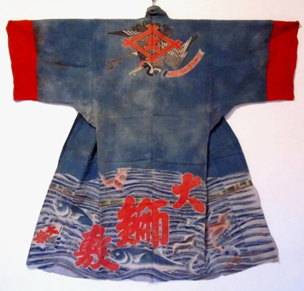 "A maiwai (fisherman's coat - this one for ceremonial occasions). The machine-made cotton from early 20th c. was stenciled with paste resist. The characters give the company name, its specialty (yellowfish), and say ""Great Catch."" Photo courtesy of the owner of the collection and the Daily Japanese Textile blog."