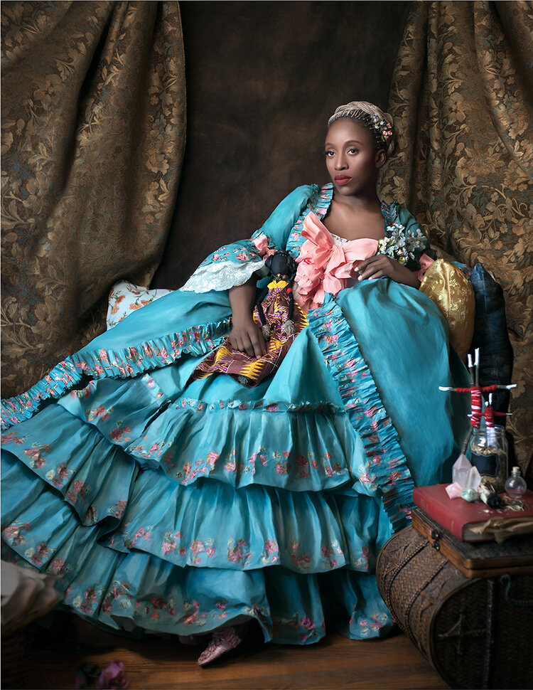 Photograph of dark skinned person reclining in front of curtains. They are wearing an 18th century Marie Antoinette style gown. Gown, made by Fabiola Jean-Louis, is blue with pink accents. And they are holding a cloth doll.
